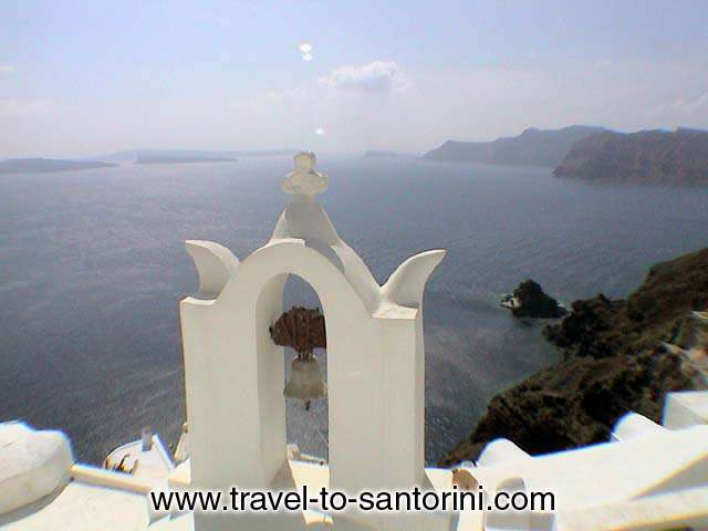 CHURCH BELL - A church bell in Oia and the view of the caldera, the Kameni islands,  Thirassia and the small islet with Agios Nikolaos church.