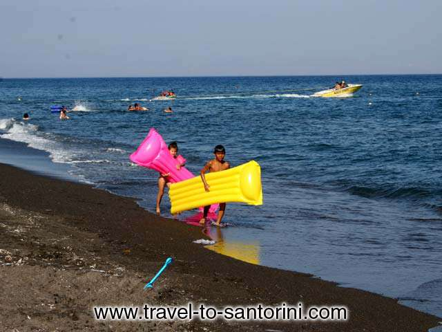 KIDS - Two kids on the beach of Agios Georgios in Santorini