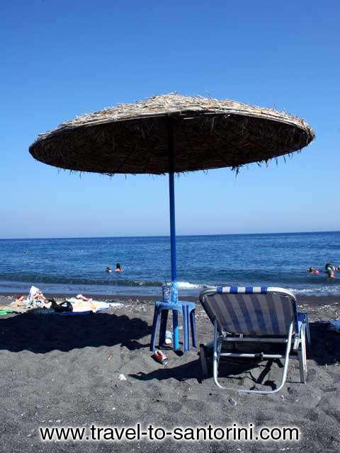 UMBRELLA - An umbrella offering shadow in Agios Georgios beach in Santorini