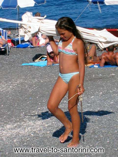 KAMARI BEACH - Girl with umbrella on Kamari beach, Santorini island