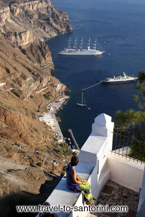 WOMAN WATCHING CALDERA - A woman at the edge of Caldera watching two cruise ships in Gialos