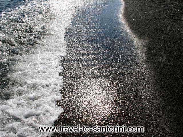 GREY SAND - The dark grey sand of Perivolos beach. While smooth it don't stick on the skin.