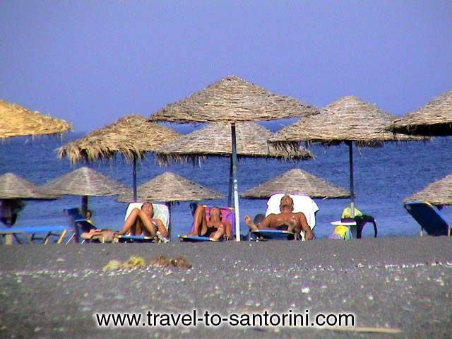PERISSA BEACH - Sunbathing in Perissa! A company enjoying the sun early in the afternoon in Perissa. by Nikos Margaritopoulos