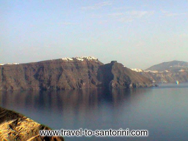 IMEROVIGLI - View of Imerovigli from Oia, Skaros rock in front of the village and<br> Theoskepasti (the small church in front of Skaros).