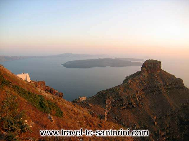 Skaros and volcano view - View of Skaros and the volcano from Imerovigli. On the left a person standing in front of Agios Giannis church.